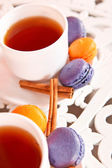 Tea cup with purple and orange macaroons and canella — Stock Photo