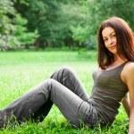春天的美丽女孩。美丽的年轻女子躺在户外的绿草上。公园。草甸。夏天。春姑娘躺在字段上 — 图库照片