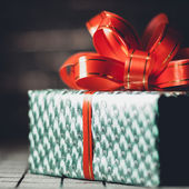 Green gift box with a red ribbon on background close-up — Stock Photo