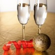 Two champagne glasses with a red ribbon and a toy — Stock Photo #33205033