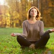 Beautiful young girl meditating in autumn park — Stock Photo #37131167