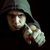 Grunge image of a depressed drug addict looking at a syringe and drugs — Stock Photo