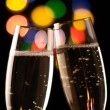Two glasses of champagne toasting against bokeh lights background — Stock Photo