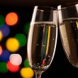 Two glasses of champagne toasting against bokeh lights background — Stock Photo #37721593