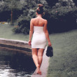 Young girl in a white dress walk coast of the river. Outdoor — Stock Photo