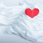 Red heart on white silk fabric — Stock Photo