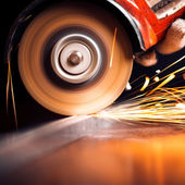 Worker cutting metal with grinder. Sparks while grinding iron — Stock Photo