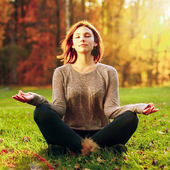 Beautiful young girl meditating in autumn park — Stock Photo