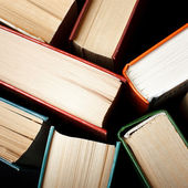 Old and used hardback books or text books seen from above. Books and reading are essential for self improvement, gaining knowledge and success in our careers, business and personal lives — Stock Photo