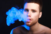 Close up portrait of young man smoking cigarette — Stock Photo