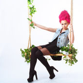 Girl with pink hair shakes on a swing — Stock Photo