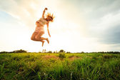 Jumping girl at field in summer — Stock Photo