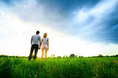 Couple walking through the field and holding hands — Stock Photo