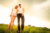 Couple walking through the field and holding hands — Stockfoto