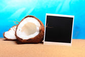 Chopped coconut and photoframe on the sand — Stock Photo