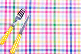 Fork and knife on a table cloth — Stock Photo
