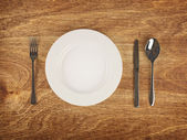 Plate and flatware on wooden table — Stock Photo