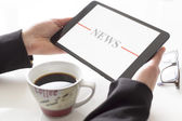Hands with tablet reading news — Stock Photo