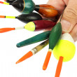 Fishing floats in hand on white background. - Stock Photo