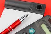 Blocco note, calcolatrice e penna su sfondo rosso — Foto Stock