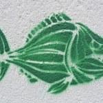 Green piranha or fish stencil graffiti on a wall — Stock Photo
