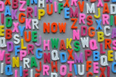 Colorful letter texture NOW word — Stock Photo
