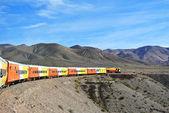 Colorful train cruising a mountain landscape — Stock Photo