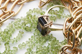 Gold necklace and ring with green peridot beads necklace — Stock Photo