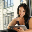 Young woman at home reading on digital tablet — Stock Photo