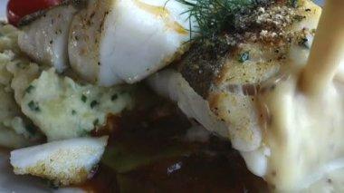 Pouring mustard sauce over white fish — Wideo stockowe