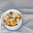 Постер, плакат: With bowl of cereal and fruit on orange tablecloth