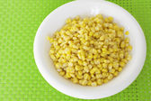 Grains of corn on green tablecloth — Stock Photo