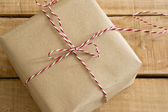 Gift box wrapped in recycled paper with ribbon bow — Stock Photo