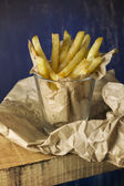 French fries in a paper wrapper, blue background  — Stock Photo