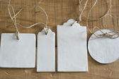 Blank tag, round, rectangular and square, on wooden background  — Stock Photo