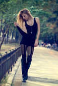 Slender fashionable woman walking outdoors — Stock Photo