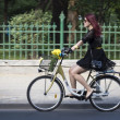Stock Photo: Womriding bicycle in Bucharest