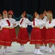 Round dance of women in red skirts and white jackets on ice — Stok Fotoğraf #23814175