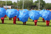 Blue umbrellas on a green field of stadium — Stock Photo