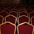Theatrical chairs with a red upholstery in a gold frame - Stock Photo