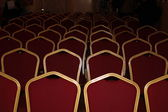 Theatrical chairs with a red upholstery in a gold frame — Stock Photo