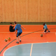 Three young athletes play balls on a blue and orange field of the sports hall — Stock Photo