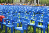 Blue plastic chairs on a green field — Stock Photo