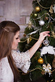 Girl decorates the Chistmas tree — Stock Photo