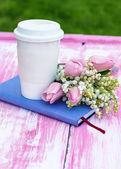Tagebuch, ein glas kaffee und lilien auf tal und tulpen — Stockfoto