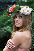Beautiful young woman with a wreath of flowers on her head — Stock Photo