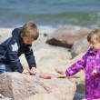 Stock Photo: Two Kids Collecting Beach Pebble