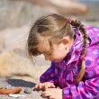 Stock Photo: Girl Examining Beach Pebble