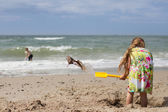 Girl in summer dress digging at beach — Stock Photo