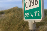 112 sign and grass-covered sand dunes — Stock Photo